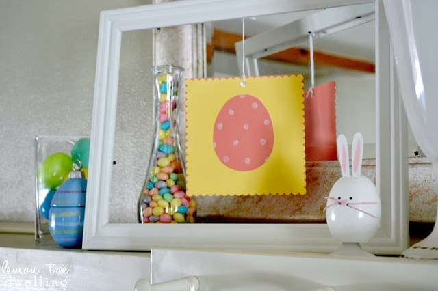 fireplace mantel decorated for Easter - Easter egg artwork, vases of jelly beans, and a whimsical bunny