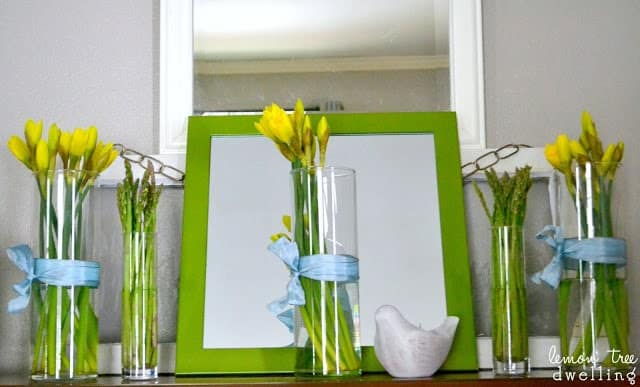 wooden mirror hand painted in spring green with a vase of yellow daffodils in front of it