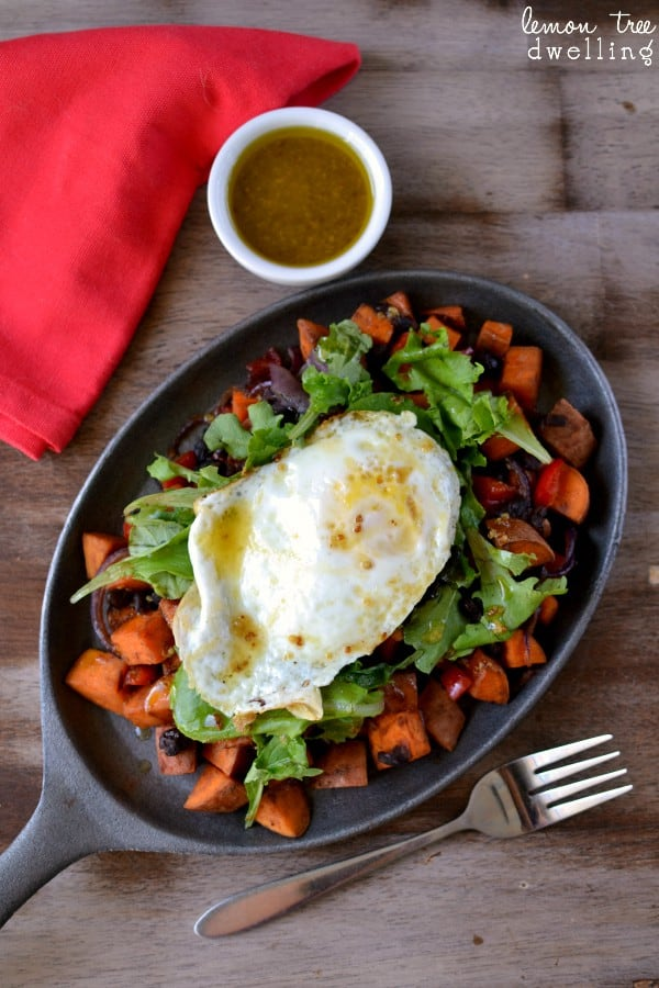 This Sweet Potato Breakfast Skillet is loaded with sweet potatoes, black beans, red bell pepper, purple onion, and a dash of hot sauce.....and topped with mixed greens, an over easy egg, and maple mustard vinaigrette. SO much flavor in one skillet!!