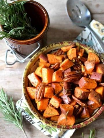 Rosemary Roasted Sweet Potatoes, simply prepared with olive oil, sea salt, fresh cracked pepper, and a touch of maple syrup, tossed with toasted pecans for extra crunch! This simply elegant side dish is perfect for any table