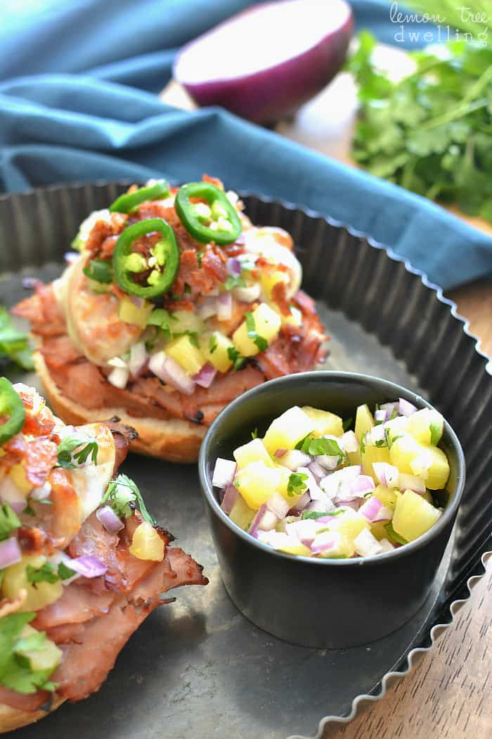 Open Face Ham & Cheese Melts topped with crispy bacon, fresh pineapple salsa, and jalapenos.