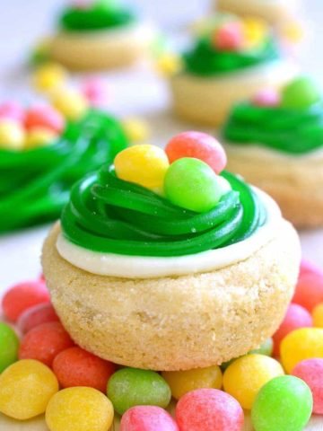 These Easter Egg Cookie Cups are easy, adorable, and so delicious! These quick and easy sugar cookies are topped with lemon buttercream, and Easter candy.