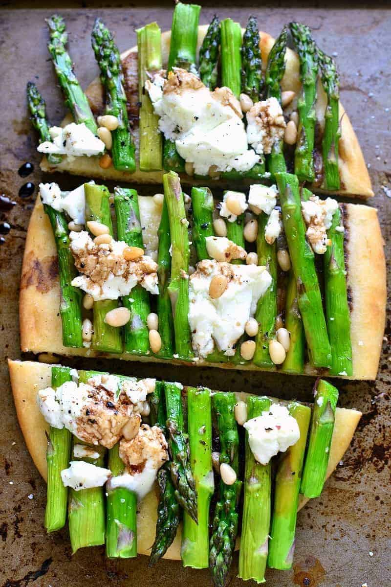 simple asparagus goat cheese vegetarian flatbread sliced into three pieces