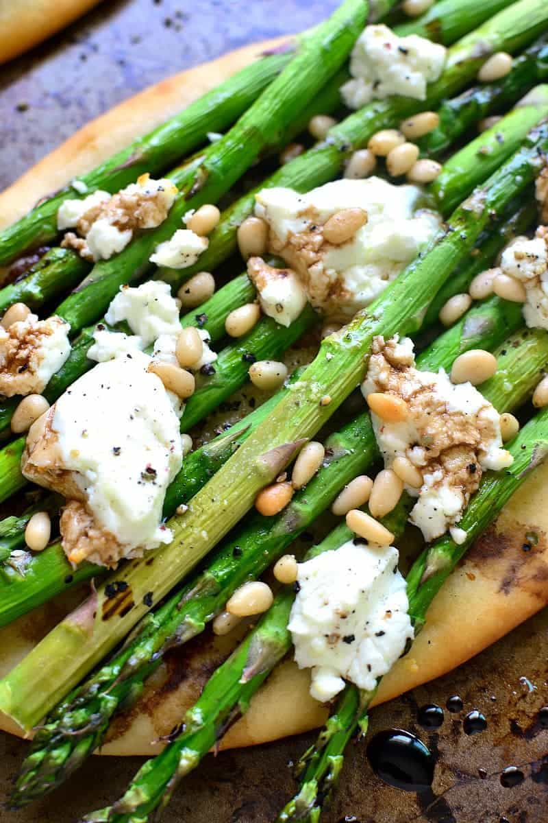 close up image of goat cheese melting over the top of asparagus and pine nuts on flatbread