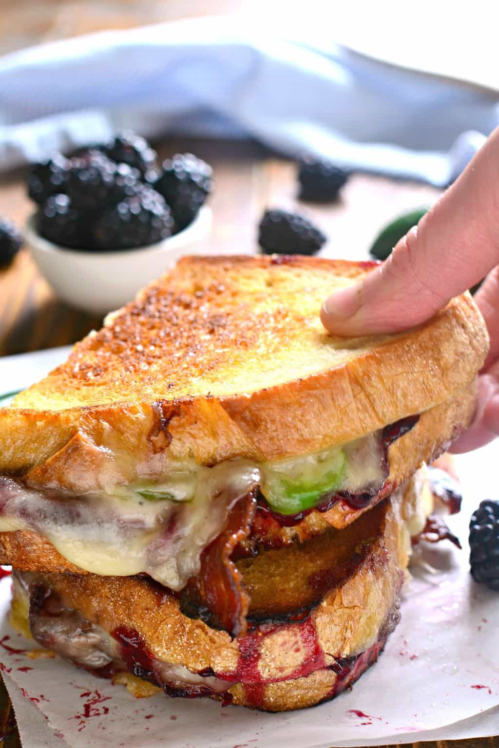 hand holding a Blackberry Bacon Grilled Cheese