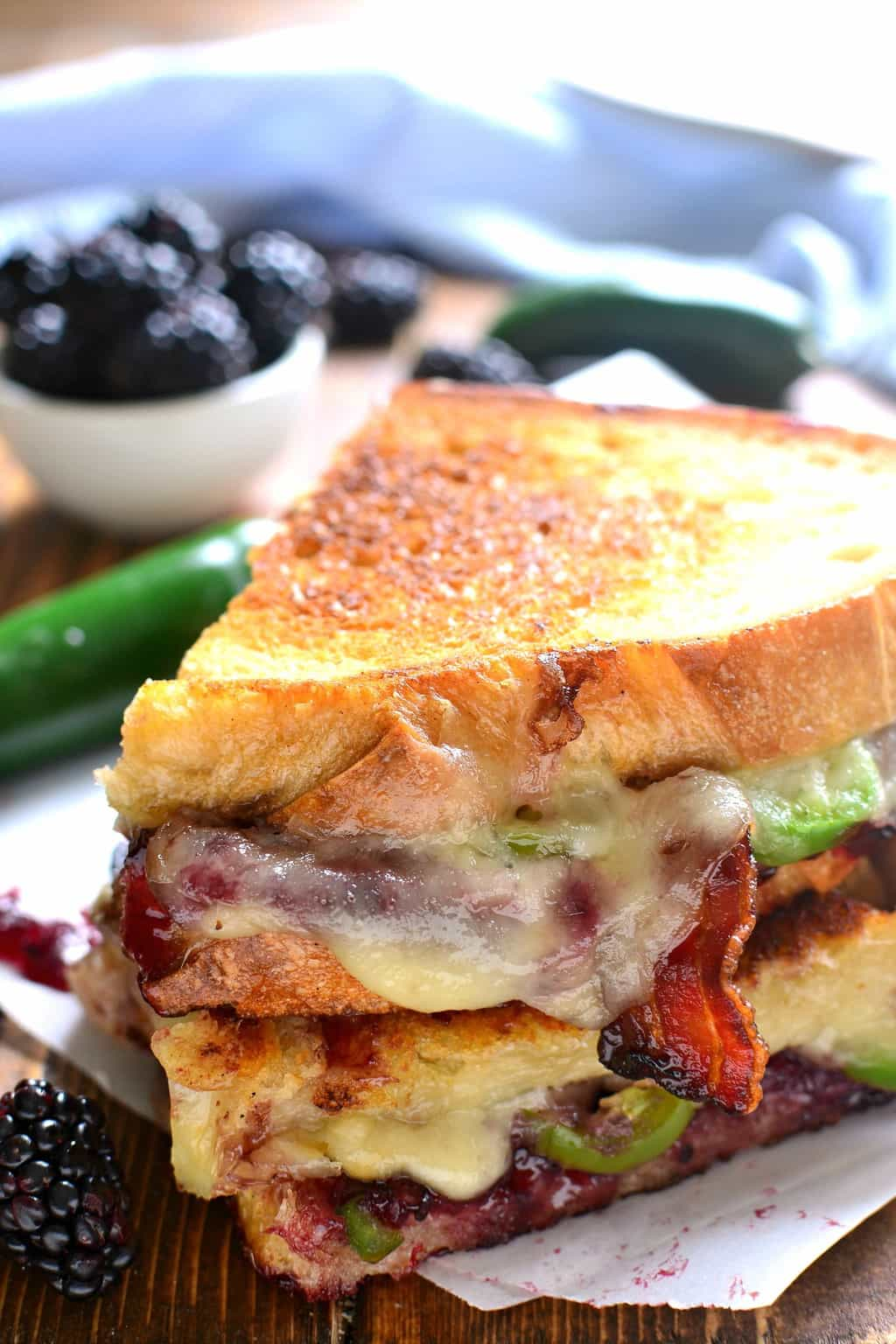 close up of melted cheese oozing down the side of a Blackberry Bacon Grilled Cheese sandwich