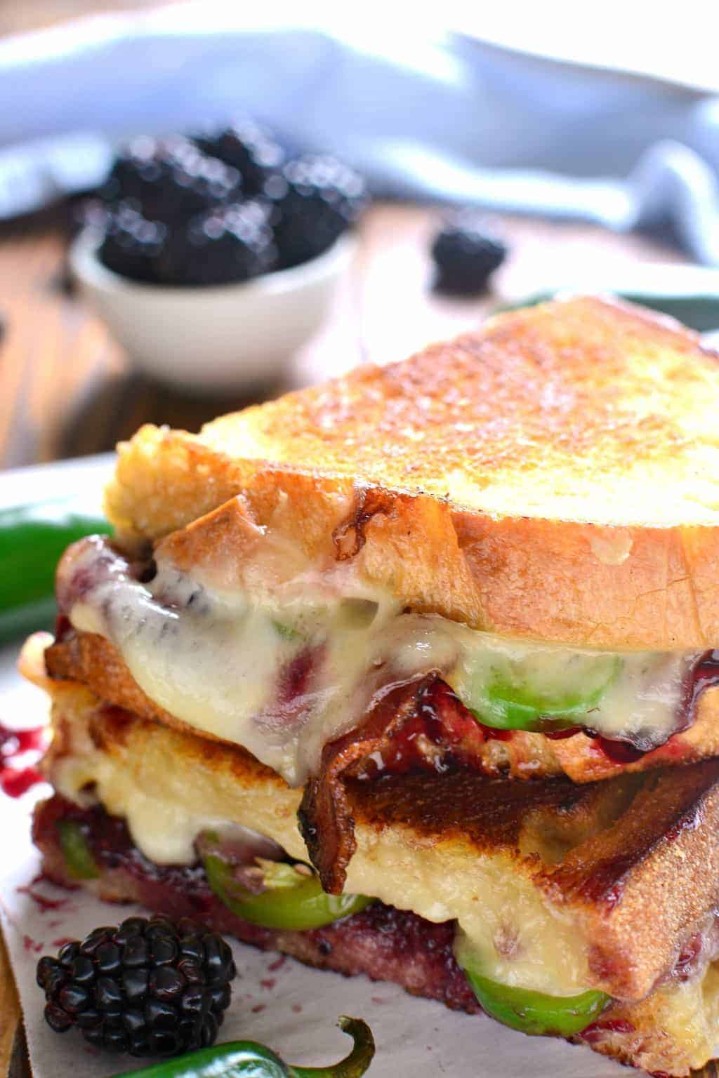 close up image of a grilled cheese sandwich on white bread with crisp bacon, jalapenos, and blackberry jam added to it.