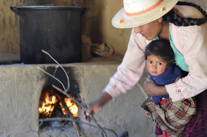 a Bolivian mother holding her baby as she stokes a wood burning stove