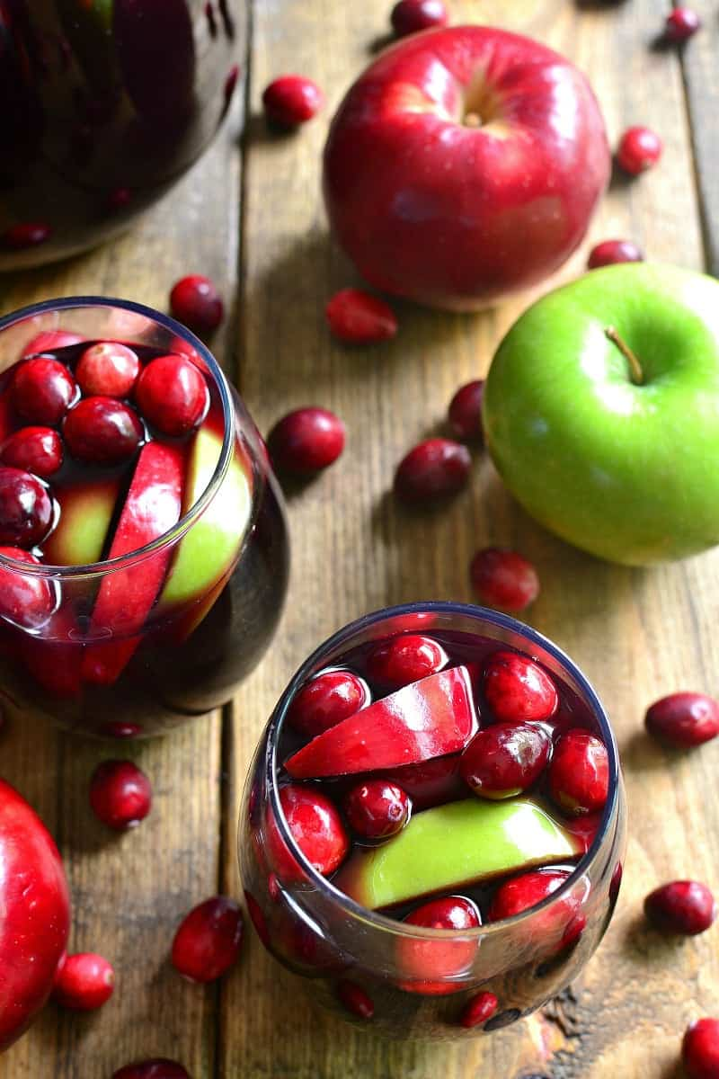 Glasses of red wine sangria with fresh cranberries and apples