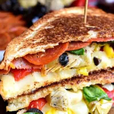 Italian Antipasto Grilled Cheese Sandwiches are a delicious twist on grilled cheese. These hot sandwiches are loaded with pepperoni, cheese, artichokes, olives, and roasted red peppers!