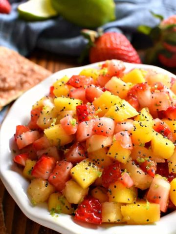 overhead image of a bowl filled with fresh fruit salsa garnished with poppy seeds