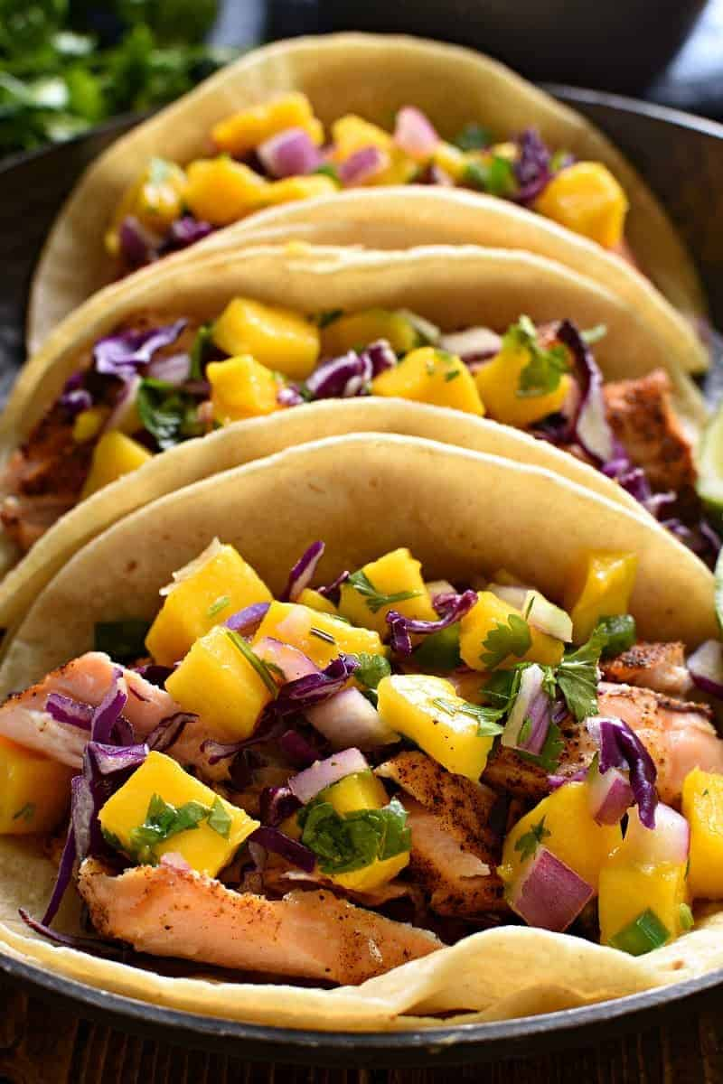 closeup image of the inside of salmon tacos with mango salsa