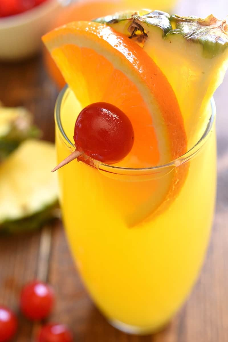 overhead image of a tropical mimosa cocktail garnished with a skewer of tropical fruit