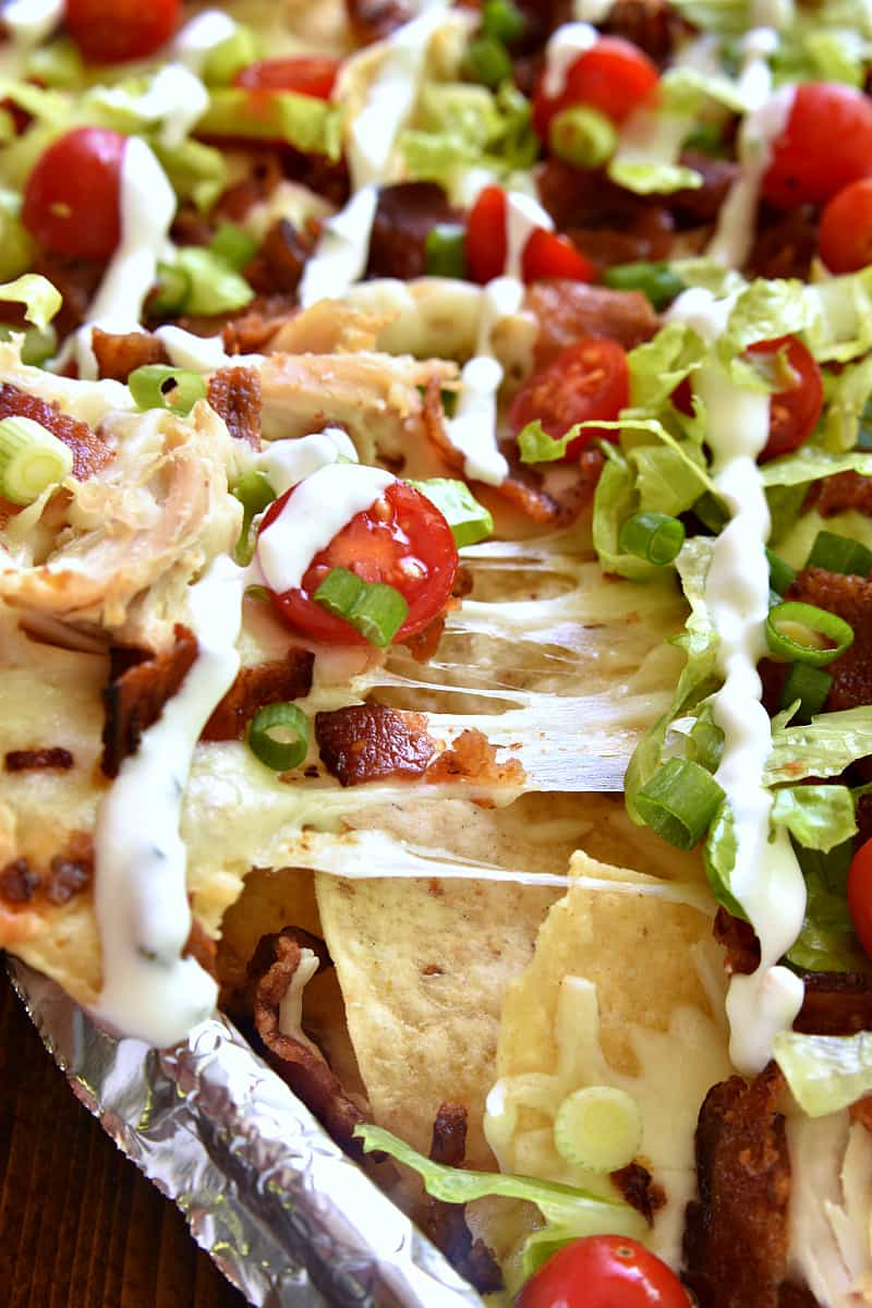 These BLT Chicken Nachos are the ultimate combo! Bacon, lettuce, and tomato come together with Monterey Jack cheese and crunchy tortilla chips in a delicious sheet pan recipe that's sure to please a crowd!