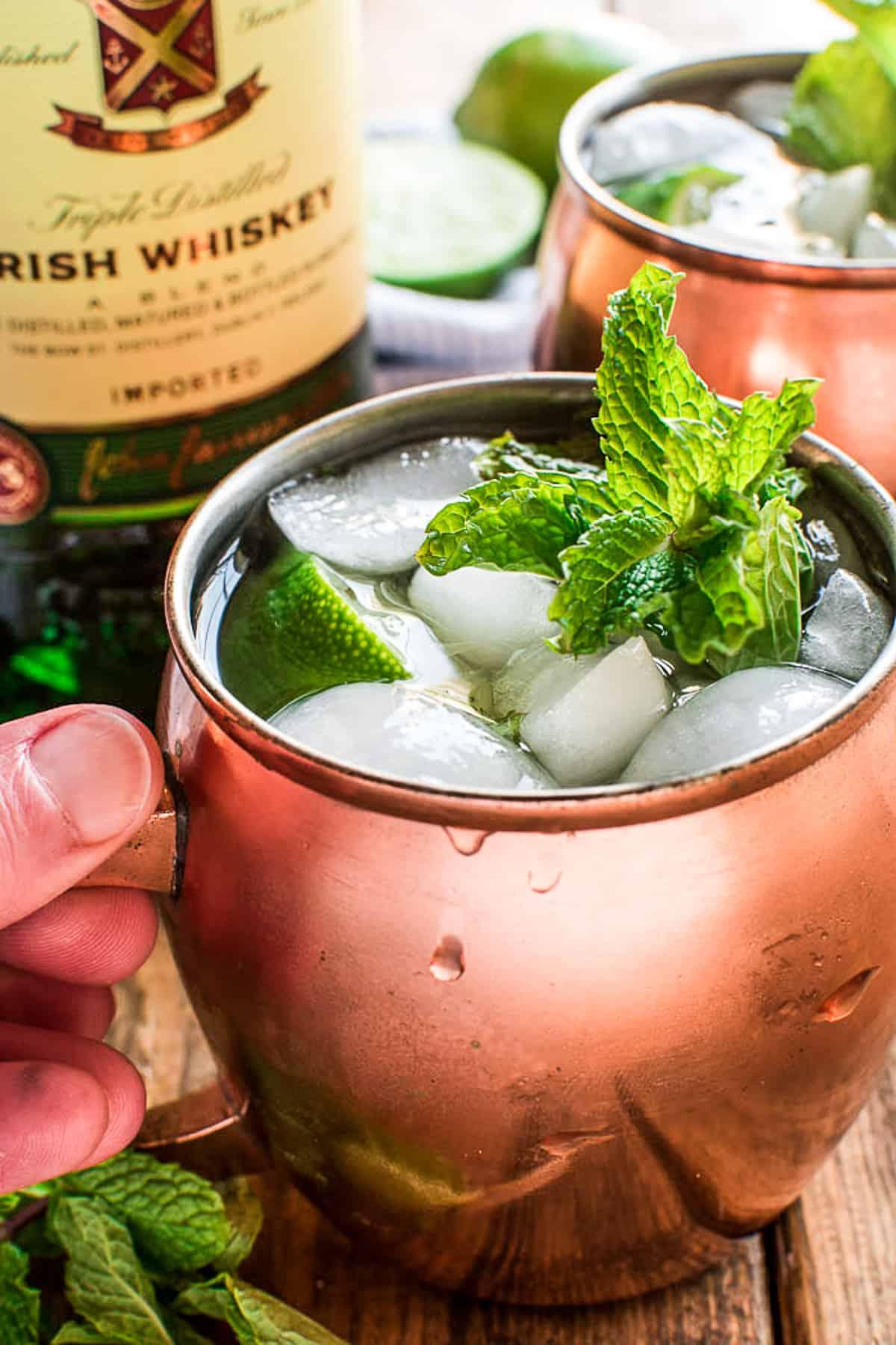 Hand grabbing copper mug with Irish Mule