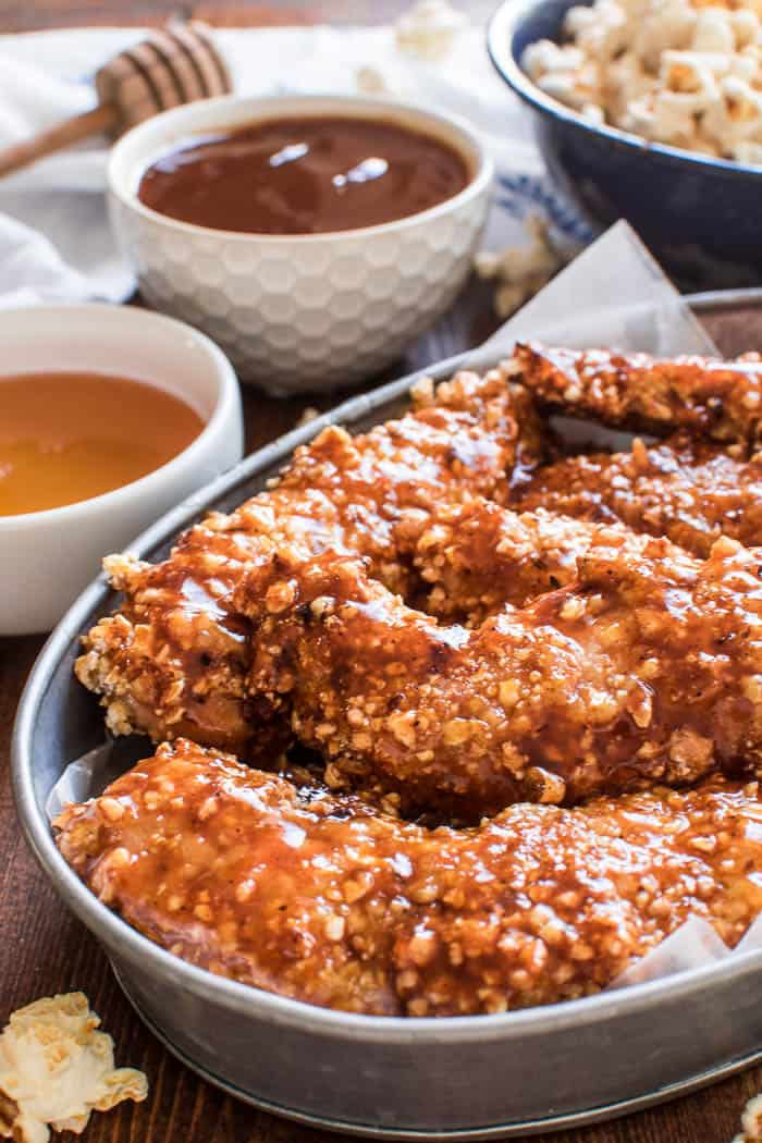 Honey BBQ Chicken Tenders are the perfect option for easy weeknight dinners! Tender, juicy chicken dipped in barbecue sauce, coated in crunchy kettle corn, and finished off with a sweet honey barbecue glaze. These chicken tenders are oven-baked and make a delicious family meal!
