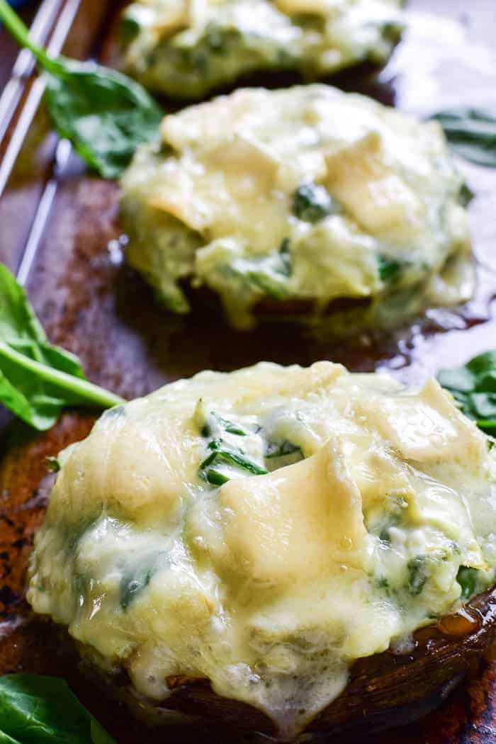 These Spinach Artichoke Stuffed Portobellos make a delicious appetizer, side dish, or meatless main dish. Loaded with a creamy blend of fresh spinach, artichoke hearts, sour cream, cheeses, and seasonings, these portobello mushroom caps are topped with brie cheese and baked to gooey perfection. @reesespecialty #sponsored