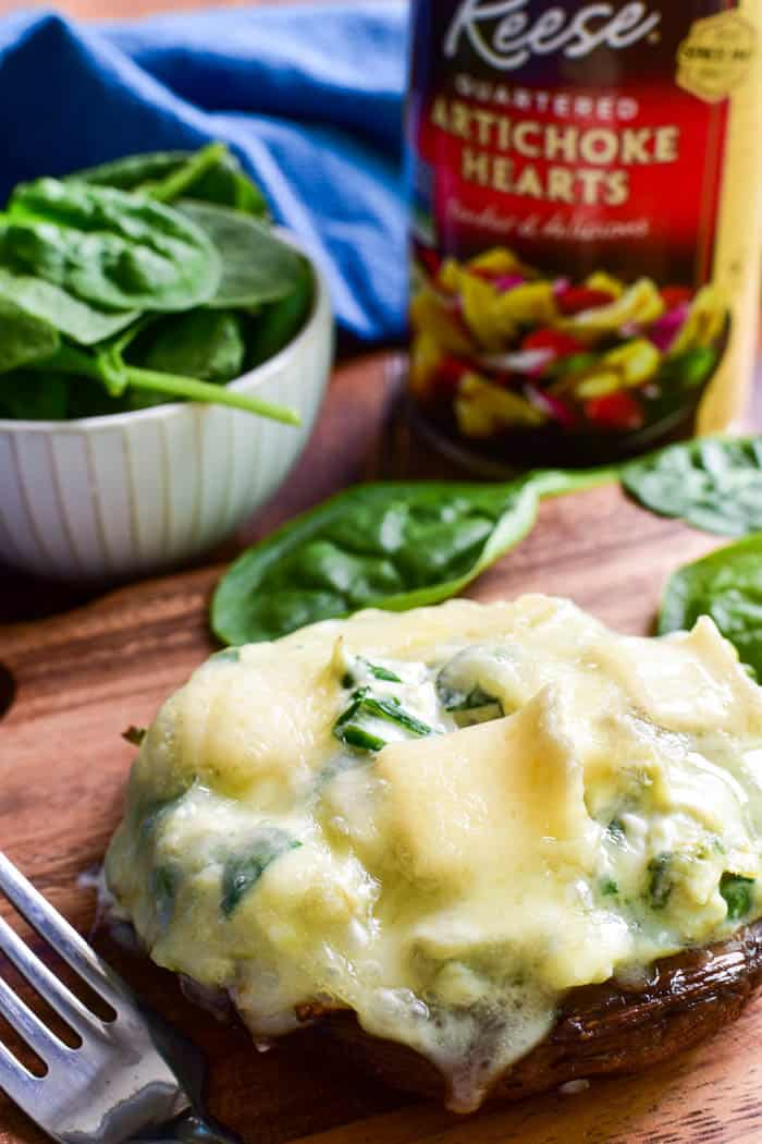 These Spinach Artichoke Stuffed Portobellos make a delicious appetizer, side dish, or meatless main dish. Loaded with a creamy blend of fresh spinach, artichoke hearts, sour cream, cheeses, and seasonings, these portobello mushroom caps are topped with brie cheese and baked to gooey perfection.