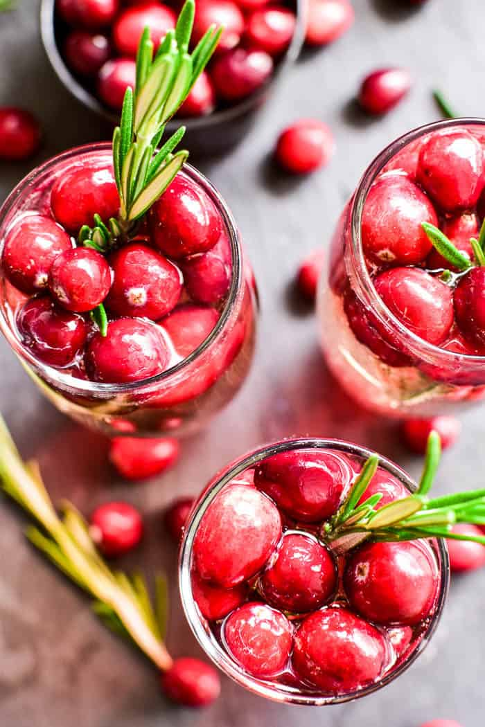 These Cranberry Mimosas are the ultimate holiday cocktail! Made with simple ingredients and garnished with fresh cranberries and a sprig of rosemary, these mimosas are sure to become your new favorite champagne cocktail. They're perfect for brunch, holiday parties, or even Christmas day. Best of all, they're made with just 3 ingredients and are easy to make by the glass or pitcherful for simple, stress-free holiday entertaining!