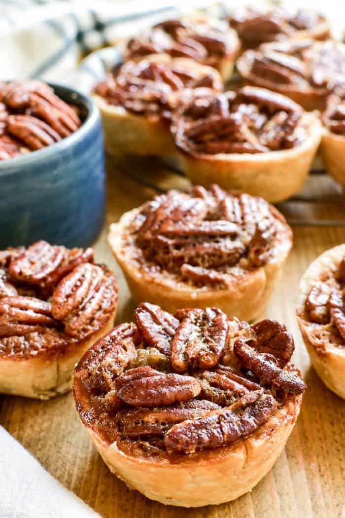 Mini Pecan Pies are the most delicious holiday treat!  Made with just a handful of ingredients, these pies come together in no time and are perfect for holiday gatherings. They have all the flavors of pecan pie you know and love, from the crunchy pecans to the gooey filling to the flaky crust. And the individual serving size makes them ideal for entertaining.