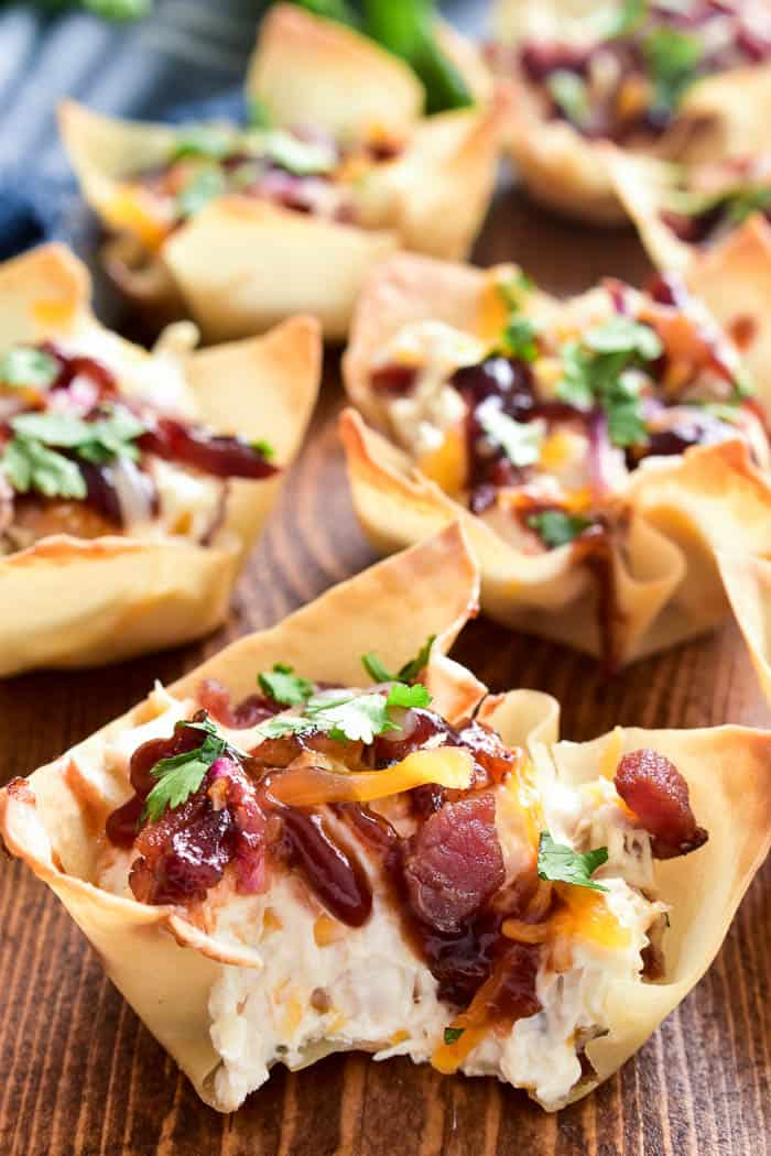 BBQ Chicken Wonton Cups are the ultimate Super Bowl appetizer! Crispy wonton shells stuffed with cream cheese, shredded chicken, and crispy bacon, then topped with shredded cheese bbq sauce, red onion, and cilantro. These cups are easy to make, ready in just 20 minutes, and perfect for game days, parties, or late night snacks. If you love bbq chicken pizza, you'll love this crunchy, creamy bite sized twist!