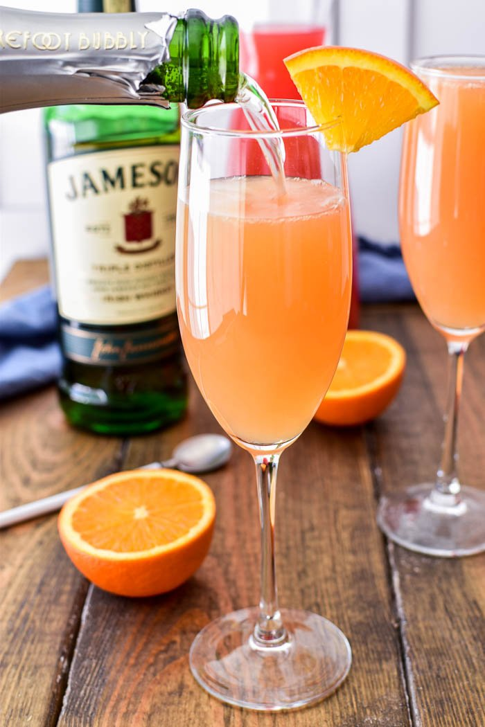 Pouring champagne into glass with mimosa