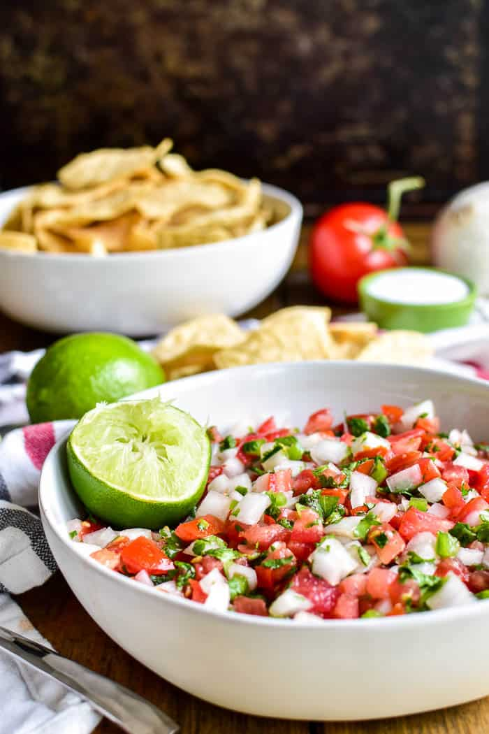 Pico de Gallo with ingredients in the background