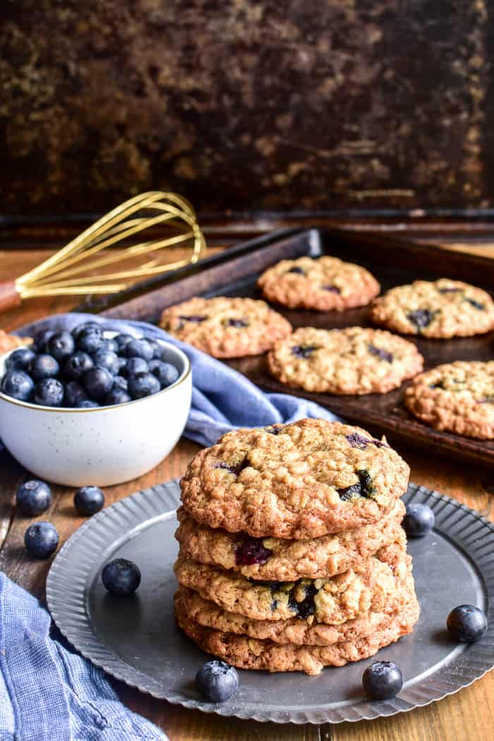 Stack of Blueberry Oatmeal Cookies on a serving tray with a bowl of blueberries in the background