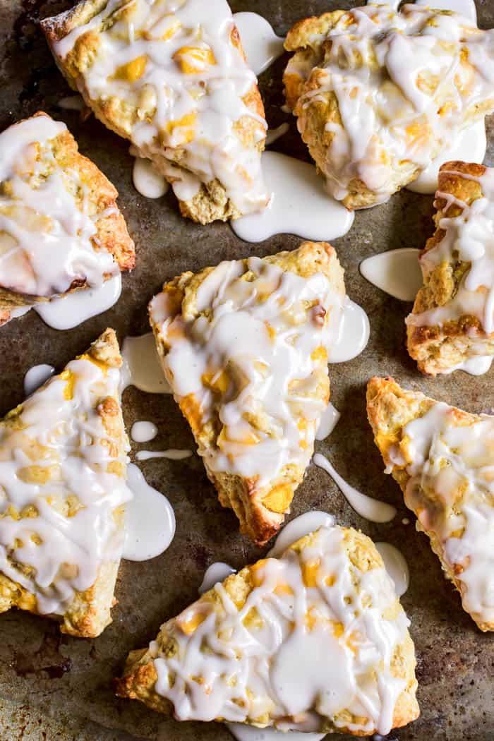 Mango Scones with glaze arranged on baking sheet