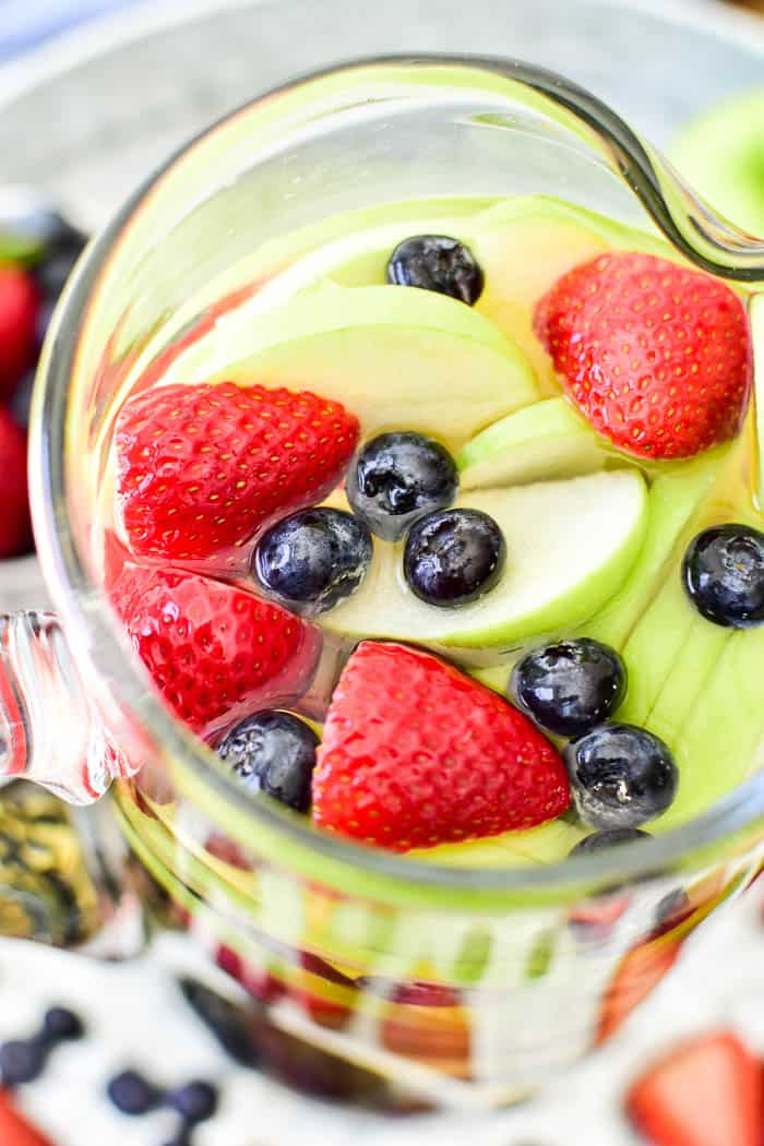 Close-up image of White Sangria with green apples, strawberries & blueberries