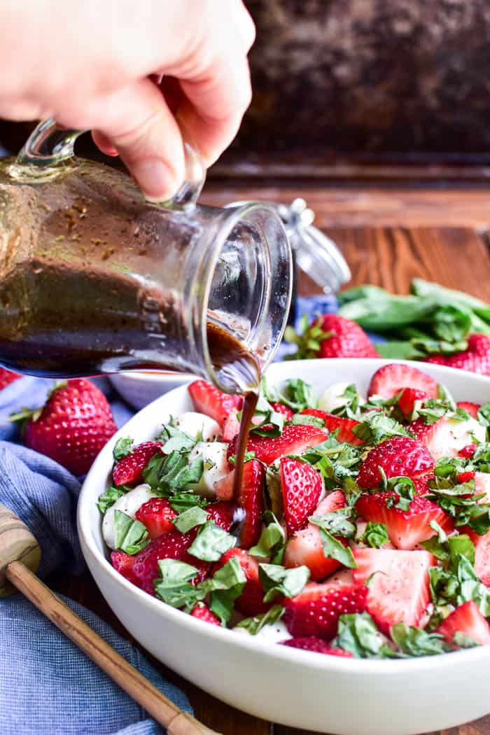 Pouring balsamic vinaigrette on Strawberry Caprese Salad