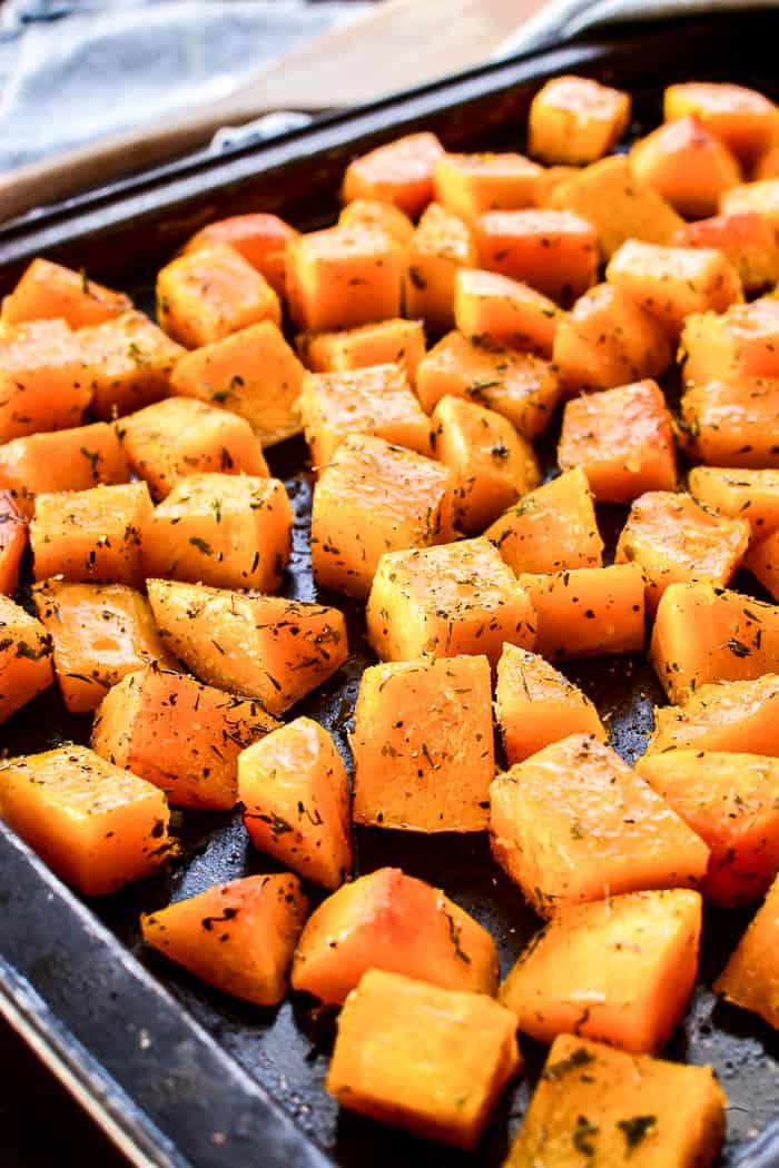 Seasoned butternut squash on roasting pan