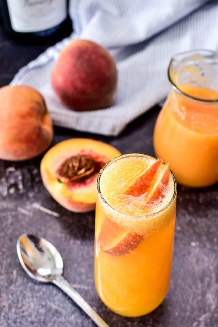 Bellini with fresh peach slices and ingredients