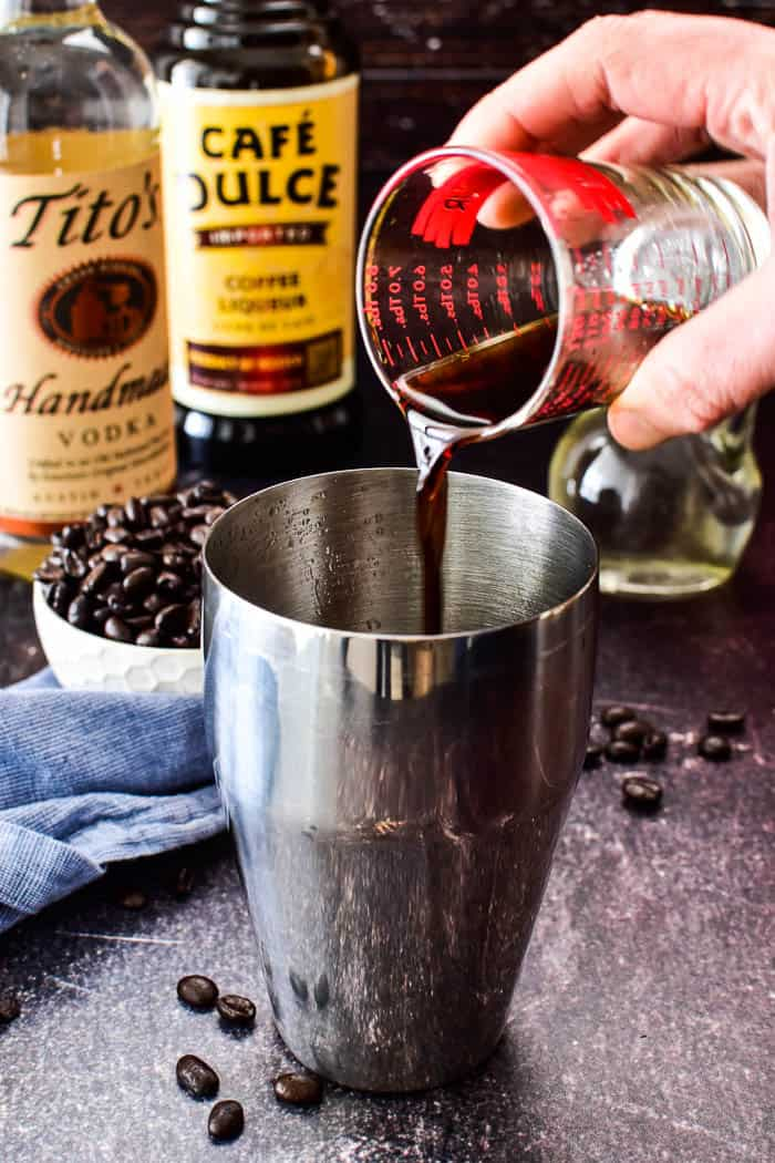 Pouring coffee liqueur into shaker for Espresso Martini