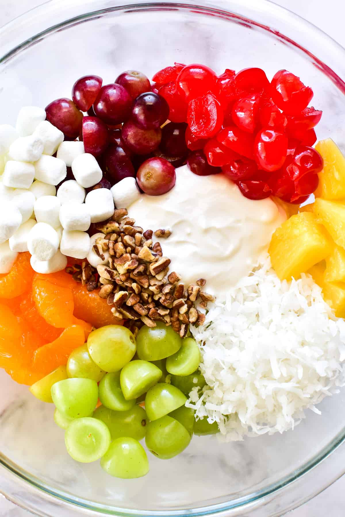 Ambrosia Salad ingredients separated in mixing bowl