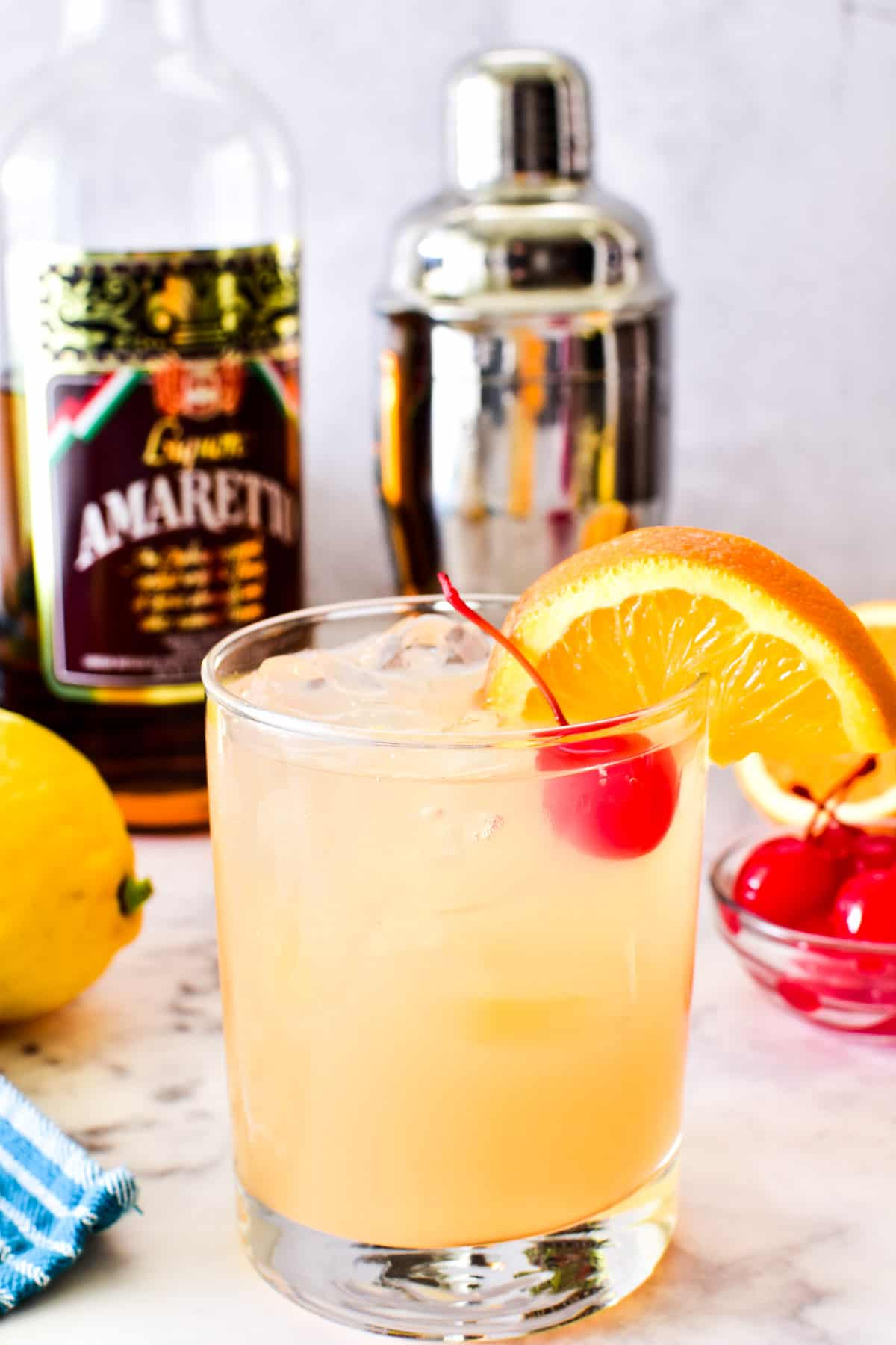 Amaretto Sour in a glass with an orange slice and maraschino cherry