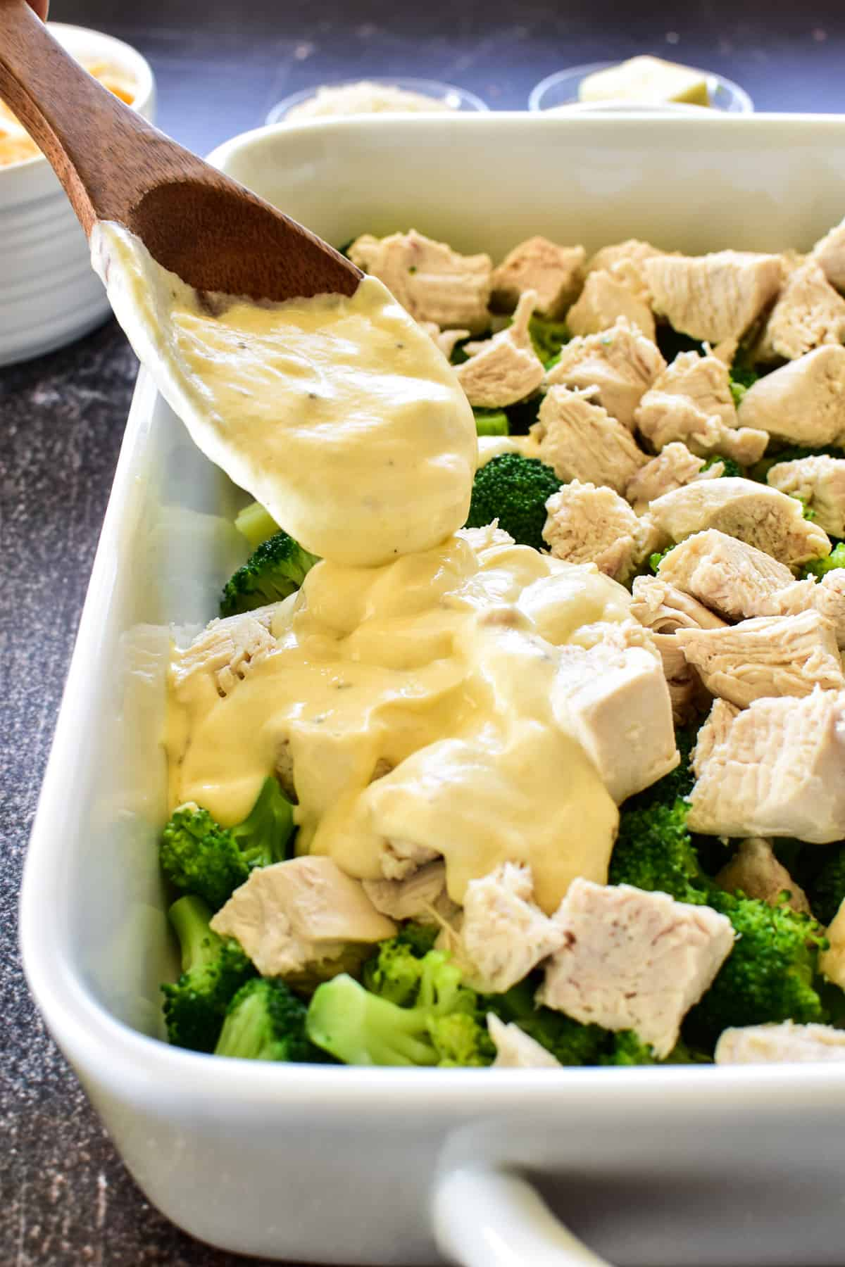 Photo of sauce layer being spooned onto chicken and broccoli