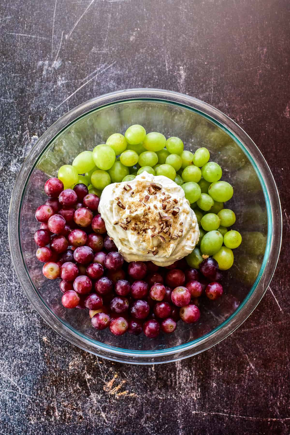 Red & green grapes in mixing bowl with dollop of cream cheese mixture