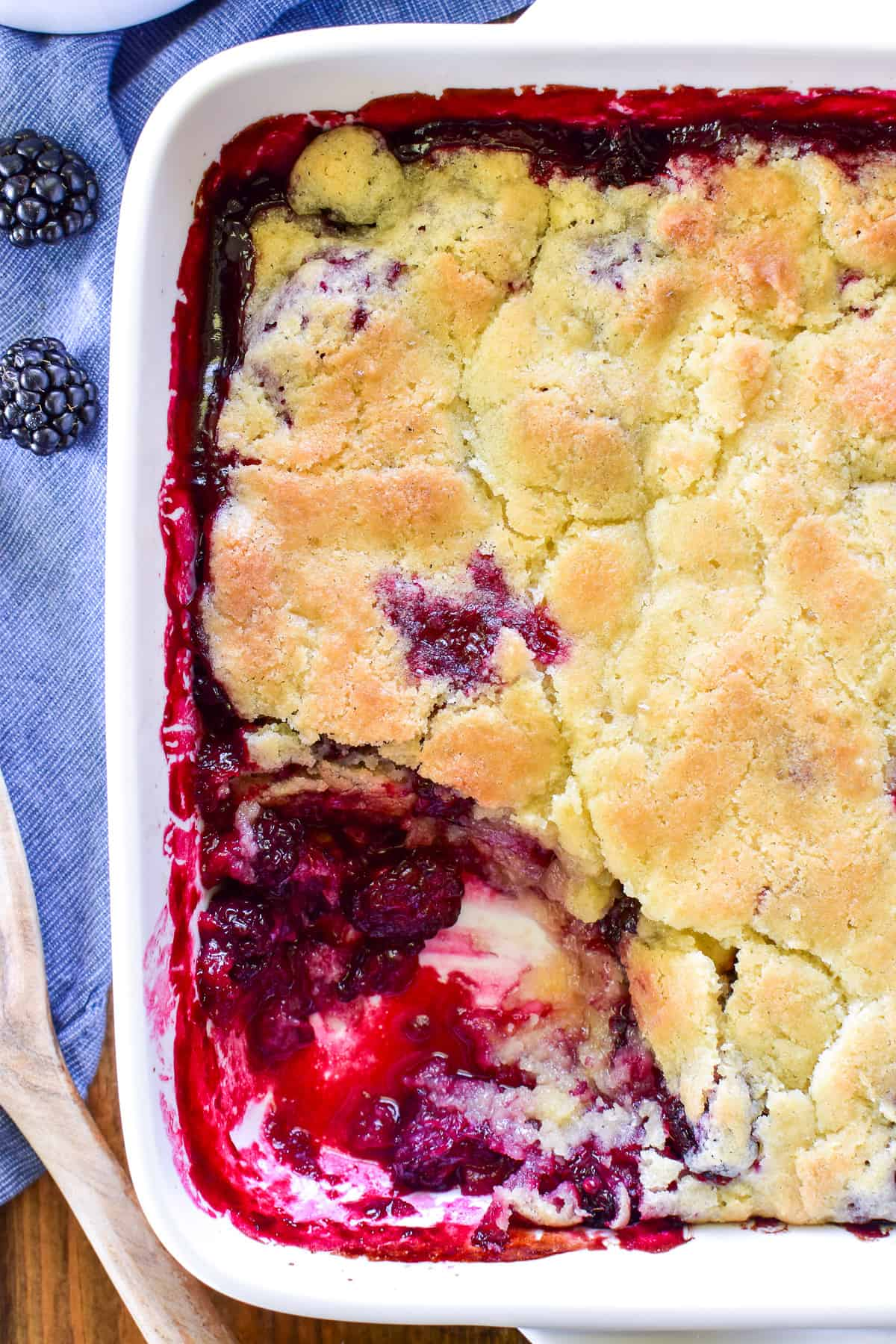 Overhead shot of Blackberry Cobbler in pan with spoonful missing