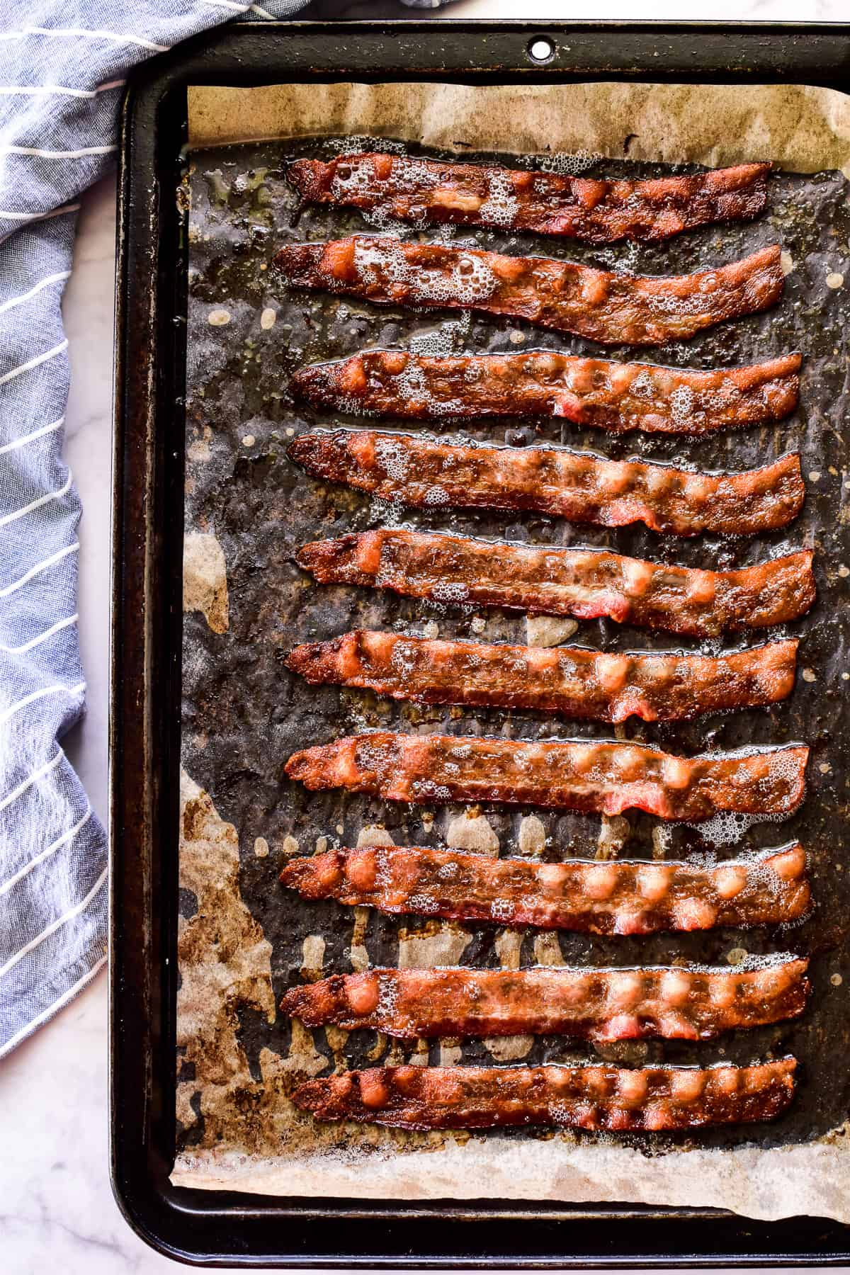 Cooked bacon on baking sheet with parchment paper