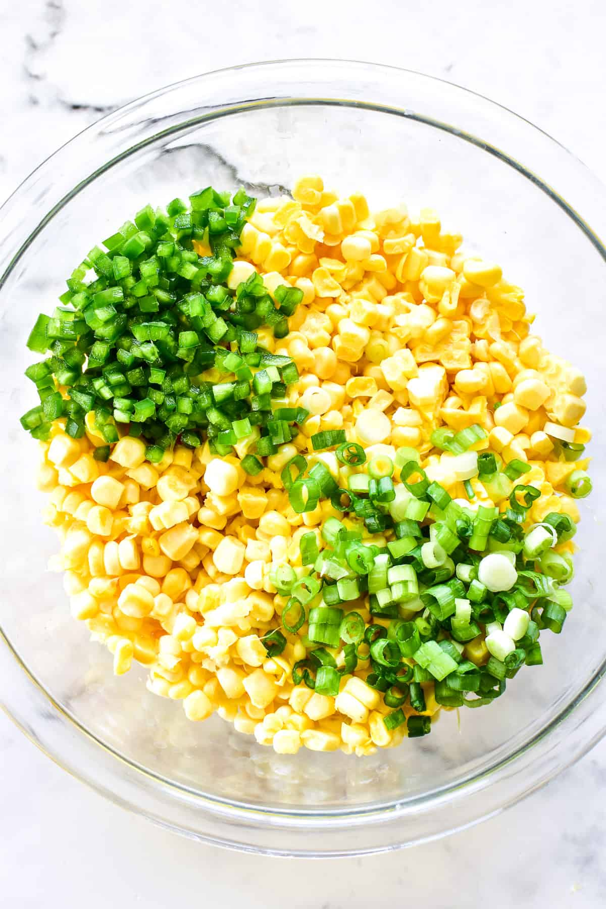 Fresh corn, minced jalapenos, and slice green onions in a mixing bowl