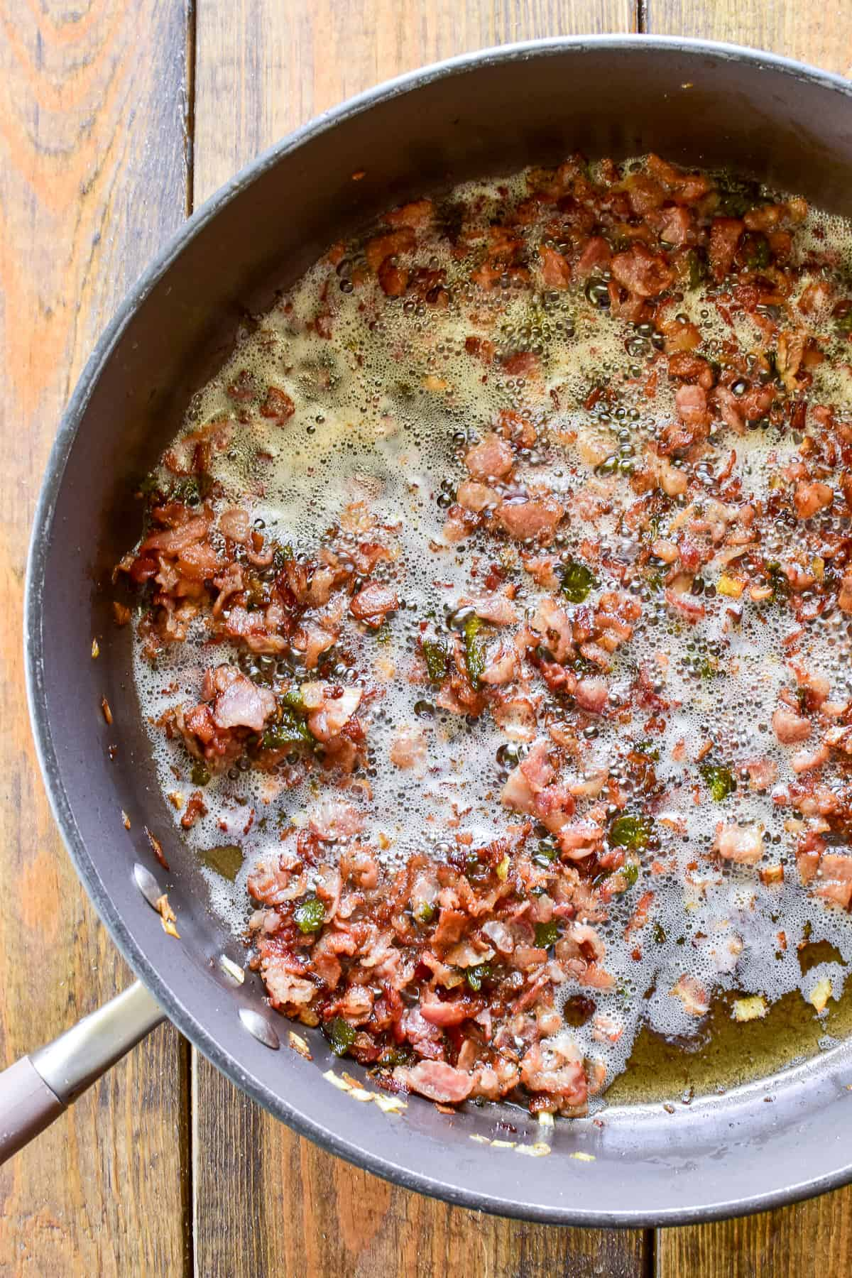 Bacon, leeks, and Poblano peppers frying in a skillet