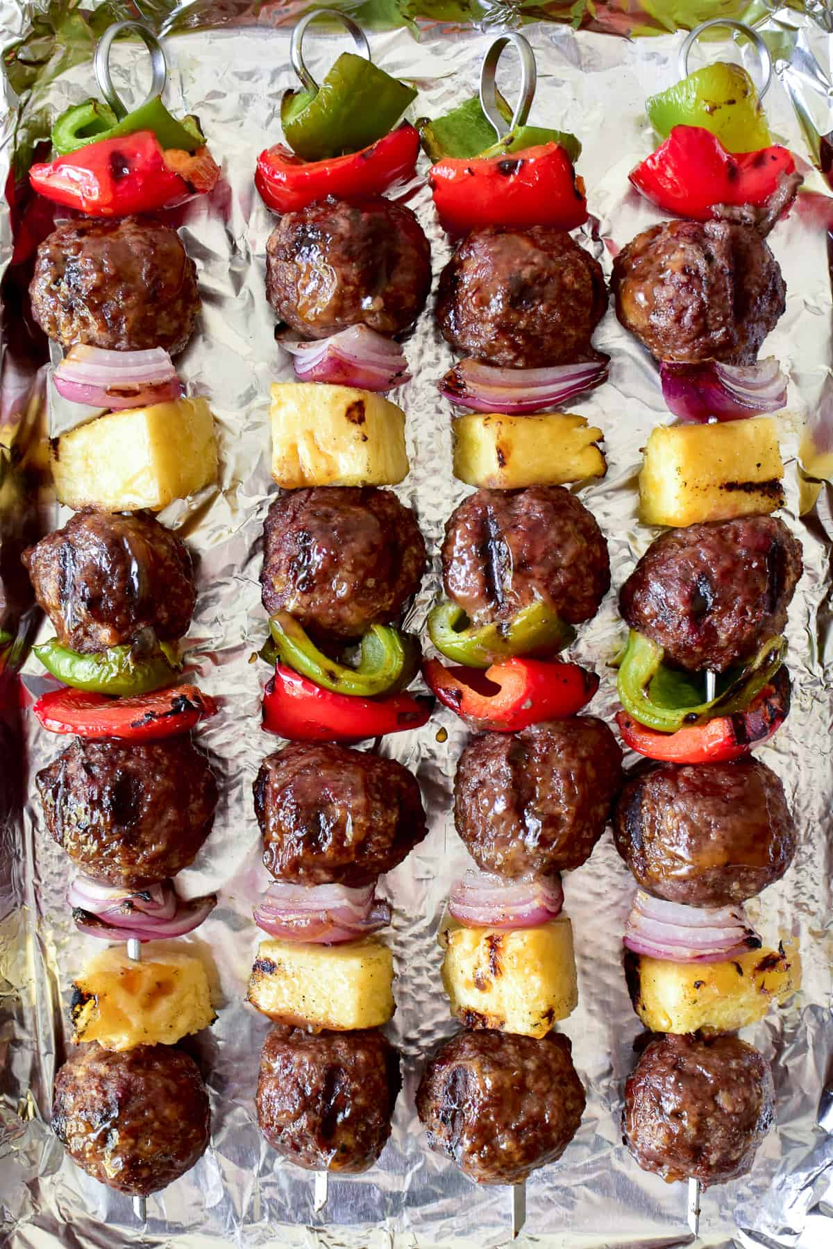 Overhead shot of Hawaiian Meatballs with peppers, onions and pineapple on skewers