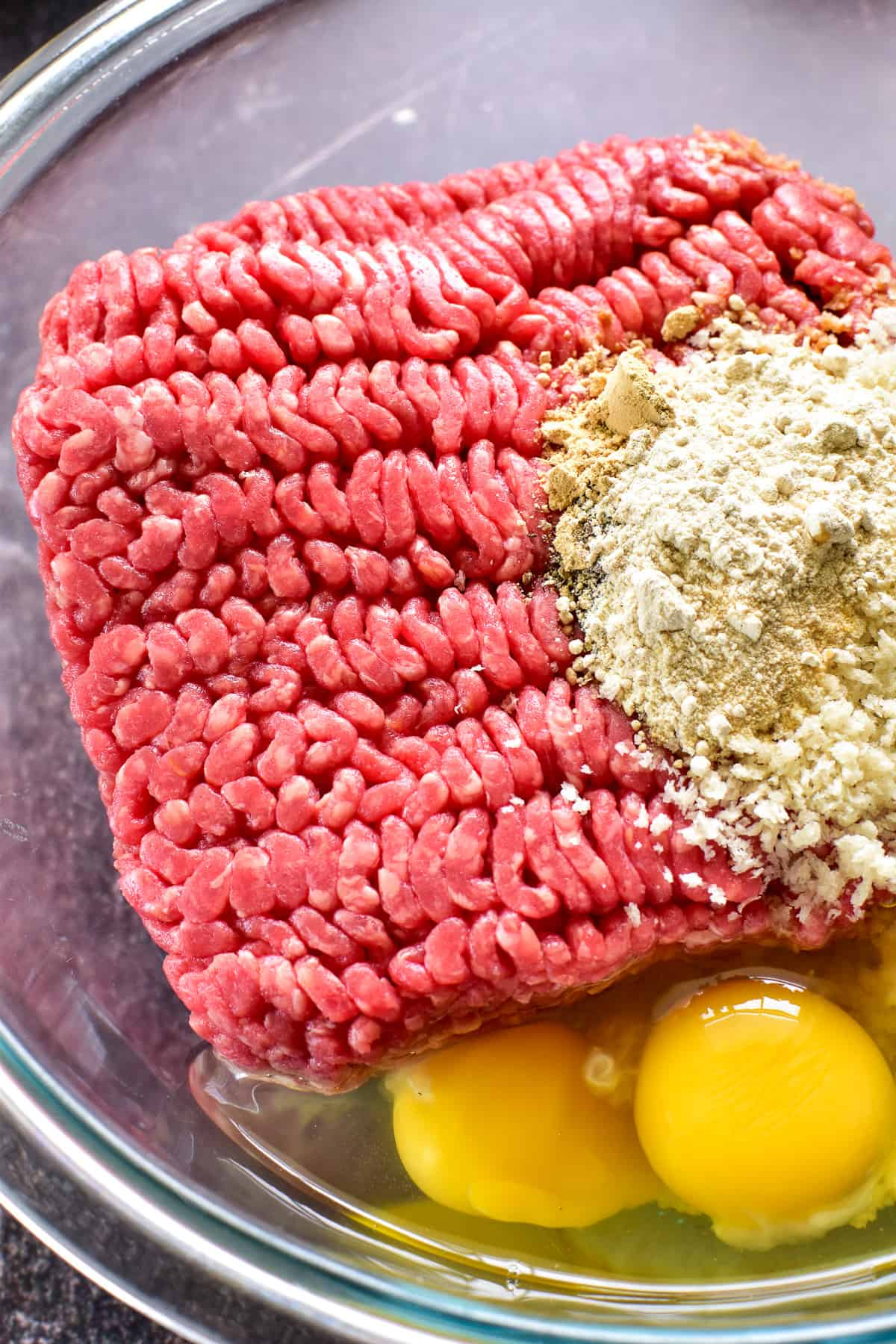 Close up of ground beef, eggs, breadcrumbs and seasonings in mixing bowl