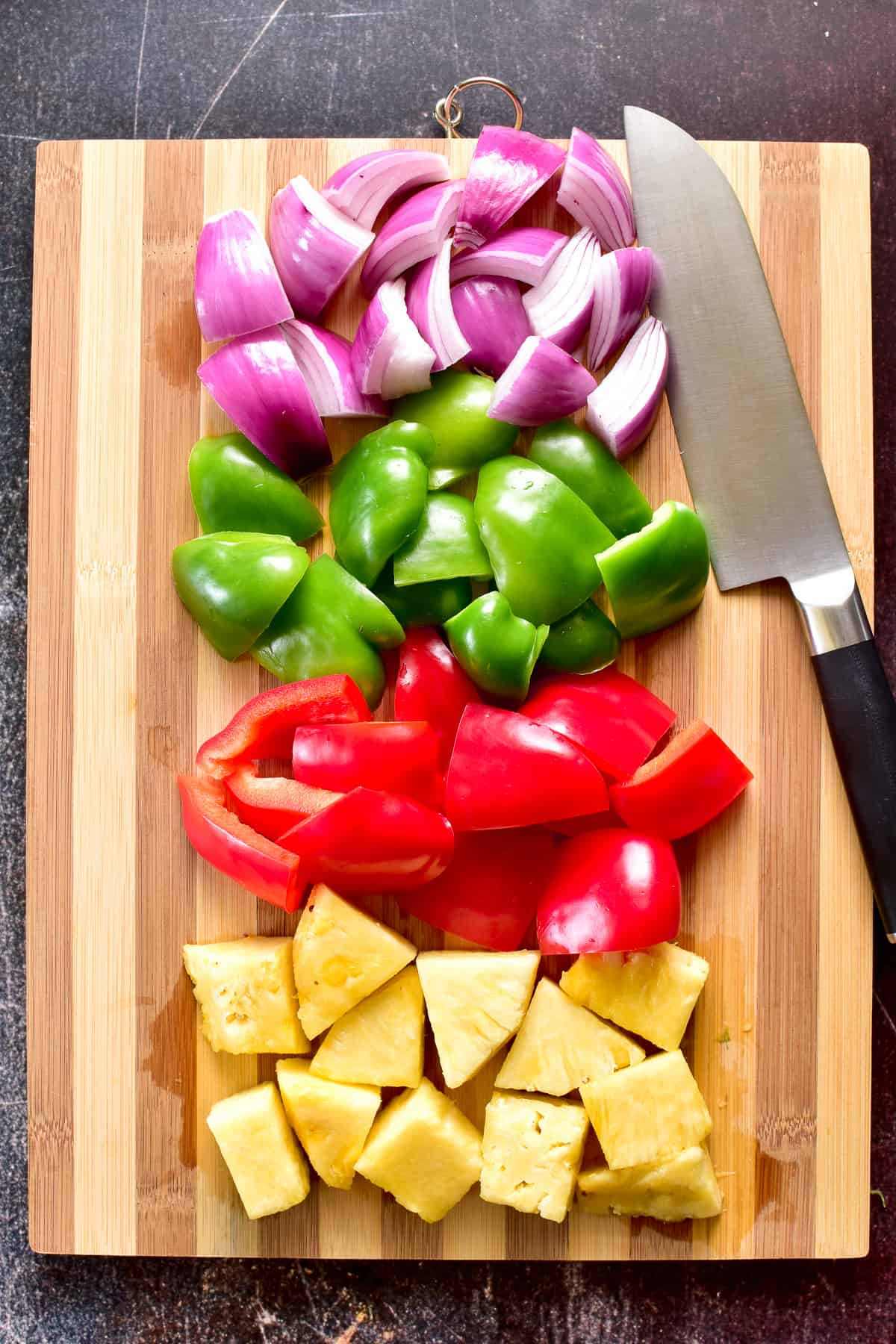 Overhead shot of peppers, onions, and pineapple chopped on a cutting board