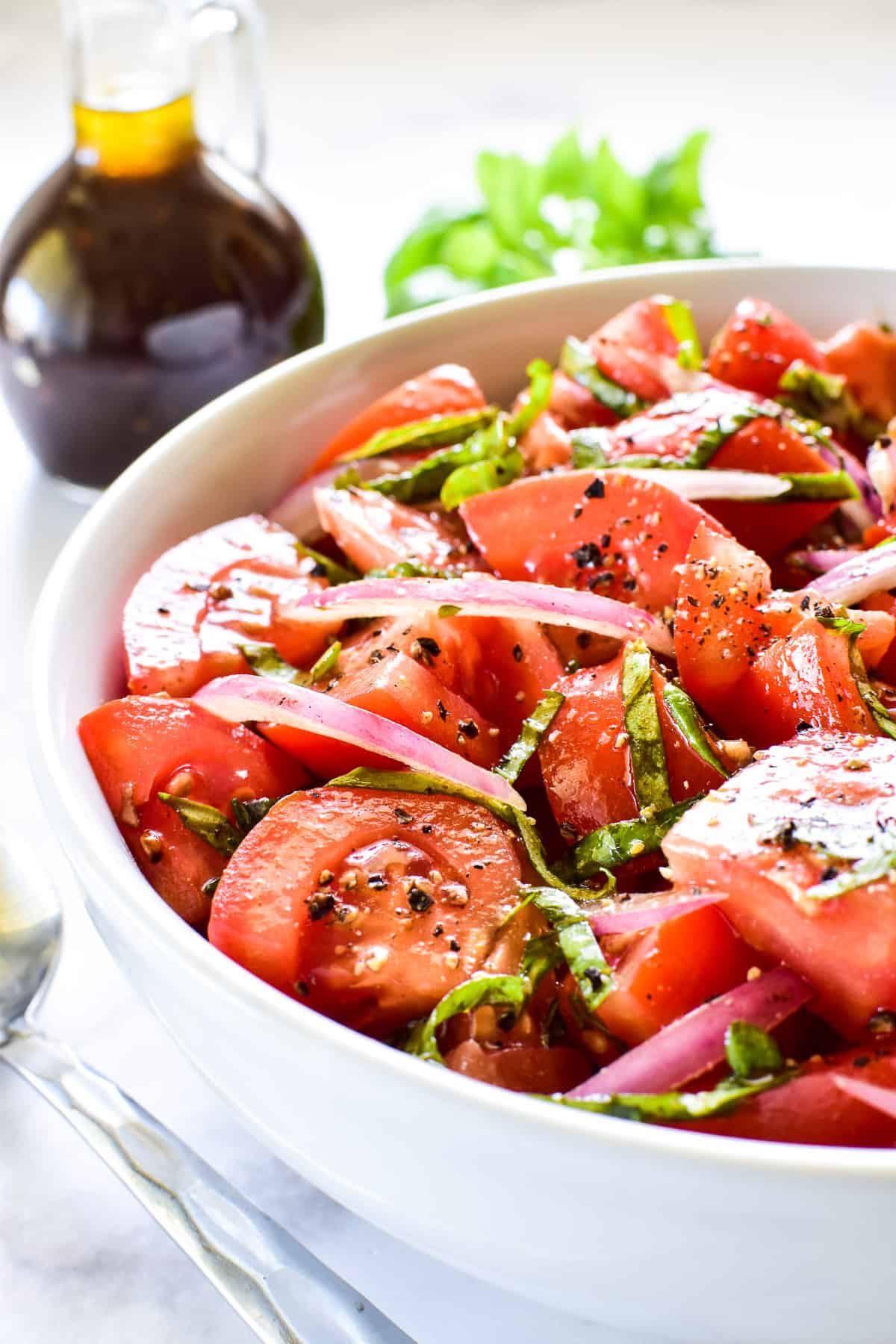 Side shot of Tomato Salad in a bowl with balsamic vinaigrette