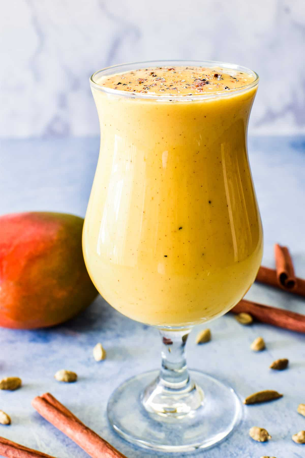 Mango Lassi in a glass with cardamom pods and cinnamon sticks