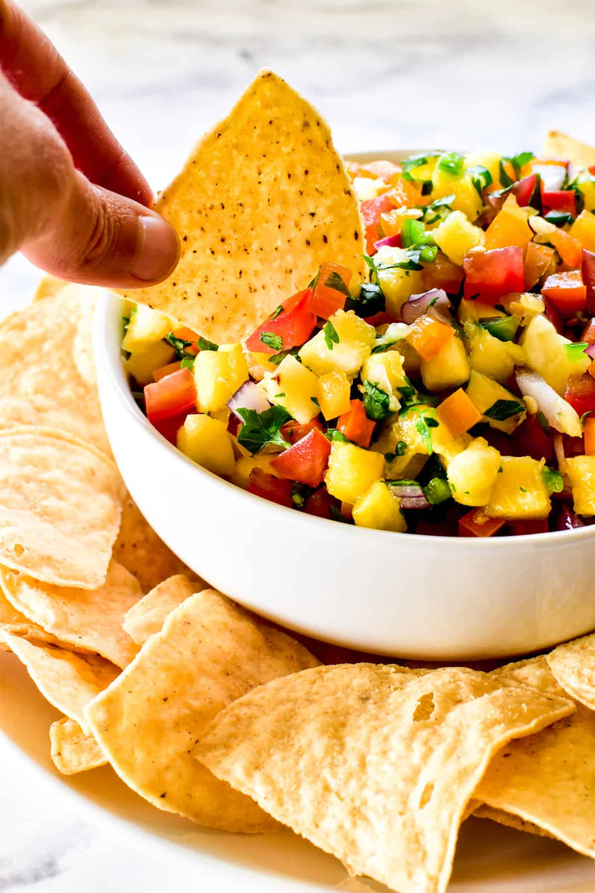 Close up of tortilla chip being dipped into pineapple salsa