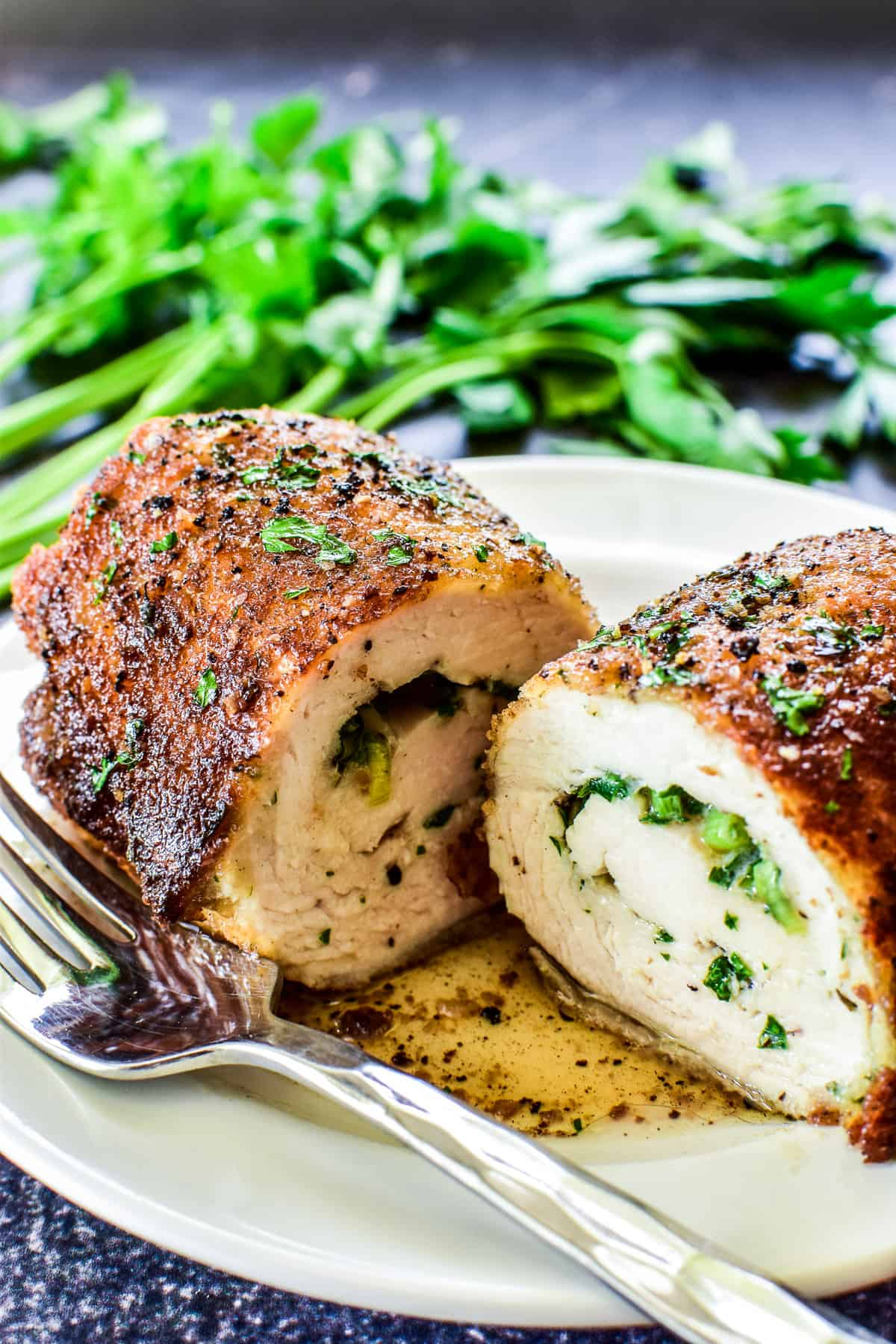 Close up of Chicken Kiev cut in half on a white plate