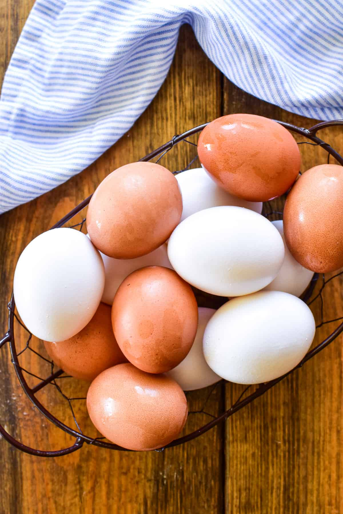White and brown eggs in a wire basket with a blue and white striped napkin